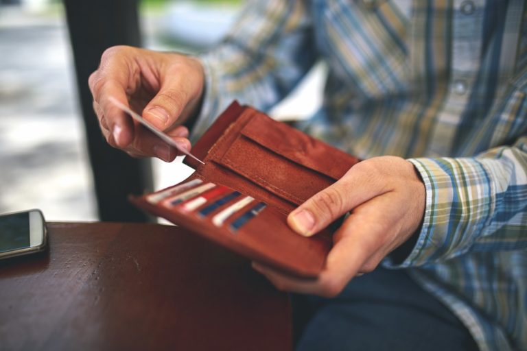 Man holding brown wallet to take out cash and credit card