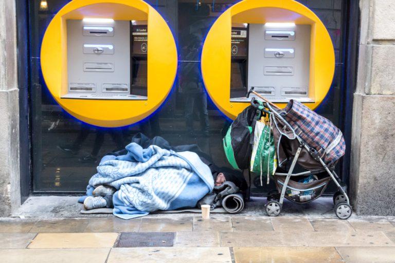 Hombre sin techo cubierto con mantas, que duerme bajo unos cajeros automáticos con un cochecito y sus pertenencias