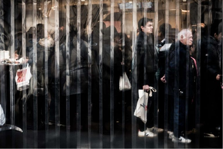 Reflection of man waiting in line holding a bag