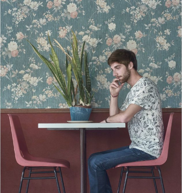 Man in floral shirt sitting on red chair against a floral wall while looking at green plant on white table